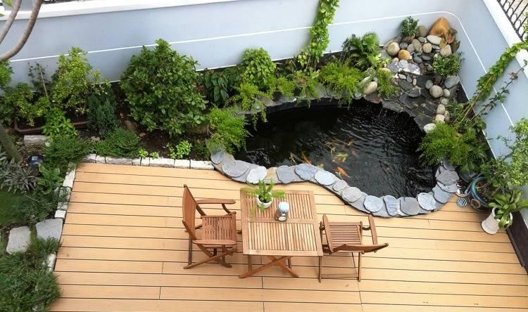 Tiểu cảnh nước nhỏ nằm bên cạnh bộ bàn ghế làm tự gỗ tự nhiên cho thấy một không gian yên bình, thư thái